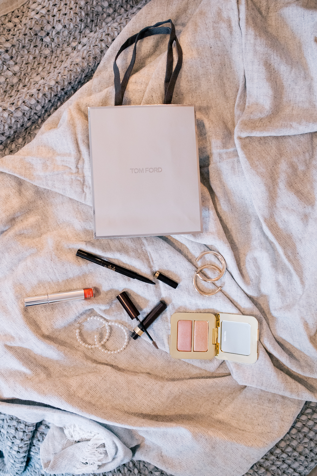 tom ford beauty bag from bloomingdale's and some makeup products on a bed