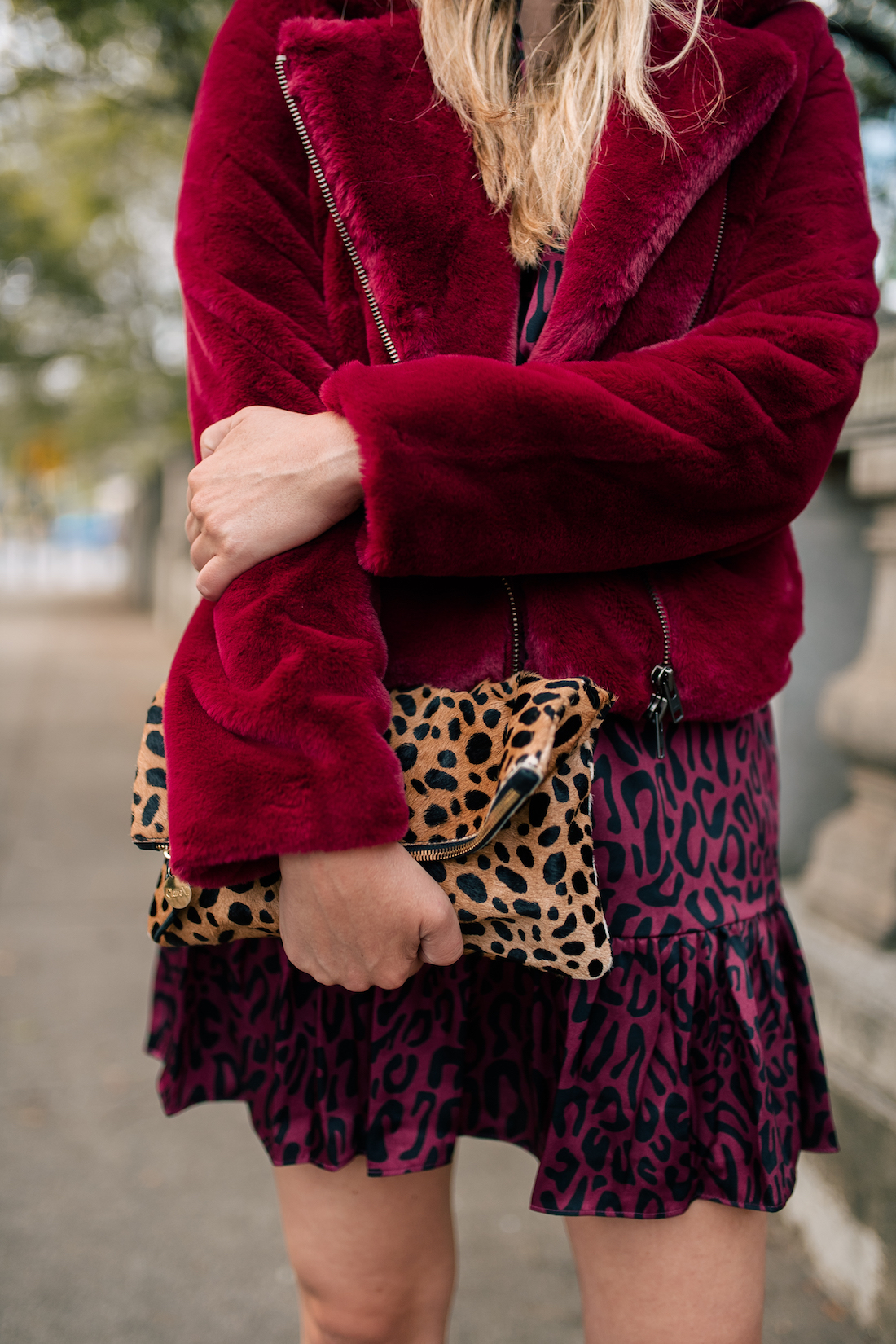 a girl holding a leopard purse and a red jacket that are part of the rebecca minkoff inclusive collection