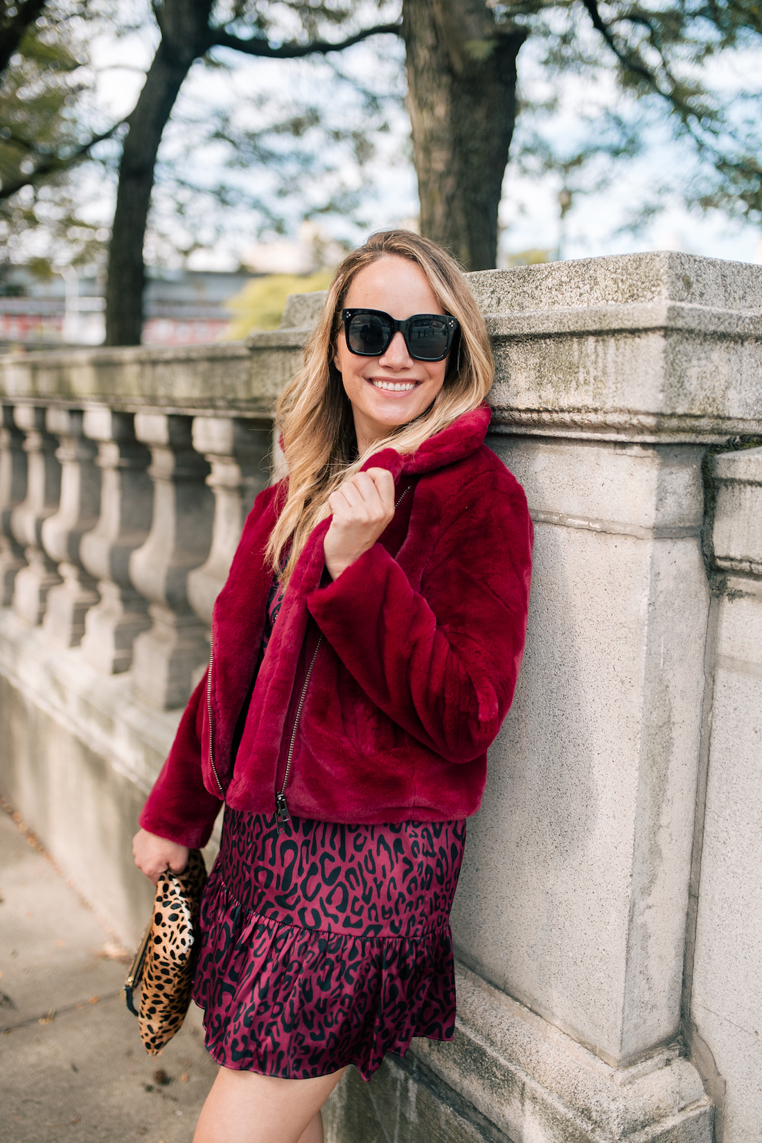 a girl with big shades and a red jacket on